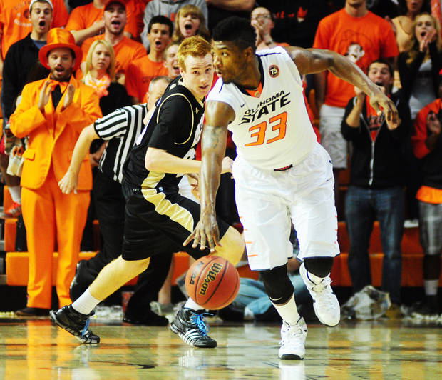 Oklahoma State sophomore guard Marcus Smart dribbles by a defender on a fast brack during an exhibition against Emporia State. Oklahoma State went on to defeat Emporia State 87-41 at Gallagher Iba Arena in Stillwater on Nov. 1, 2013.   Photo by KT King/For the Oklahoman