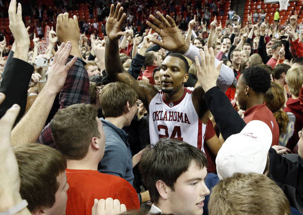 Oklahoma&#039;s Romero Osby (24) is surrounded by fans on the floor after the University of Oklahoma Sooners (OU) defeat the Kansas Jayhawks (KU) 72-66 in NCAA, men&#039;s college basketball at The Lloyd Noble Center on Saturday, Feb. 9, 2013 in Norman, Okla. Photo by Steve Sisney, The Oklahoman