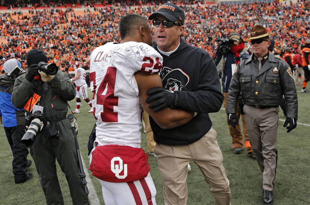Oklahoma State coach Mike Gundy congratulates Oklahoma's Brennan Clay (24) during the Bedlam college football game between the Oklahoma State University Cowboys (OSU) and the University of Oklahoma Sooners (OU) at Boone Pickens Stadium in Stillwater, Okla., Saturday, Dec. 7, 2013. Photo by Chris Landsberger, The Oklahoman