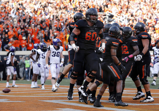 CELEBRATION: Oklahoma State celebrates a Charlie Moore (17) touchdown during a college football game between Oklahoma State University (OSU) and Texas Christian University (TCU) at Boone Pickens Stadium in Stillwater, Okla., Saturday, Oct. 27, 2012. Photo by Sarah Phipps, The Oklahoman