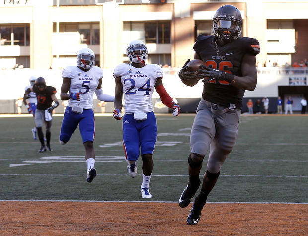 Oklahoma State's Desmond Roland (26) runs in for a touchdown as KU's JaCorey Shepherd (24) and Isaiah Johnson (5) chase him down during a college football game between the Oklahoma State University Cowboys (OSU) and the University of Kansas Jayhawks (KU) at Boone Pickens Stadium in Stillwater, Okla., Saturday, Nov. 9, 2013. Photo by Sarah Phipps, The Oklahoman
