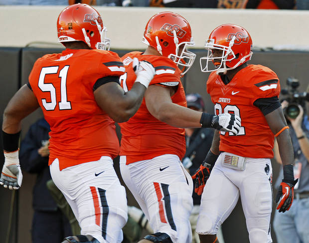 CELEBRATION: Oklahoma State's Isaiah Anderson (82) celebrates after a touchdown with Oklahoma State's Brandon Webb (51) and Lane Taylor (68) during a college football game between Oklahoma State University (OSU) and Texas Tech University (TTU) at Boone Pickens Stadium in Stillwater, Okla., Saturday, Nov. 17, 2012.  Photo by Bryan Terry, The Oklahoman