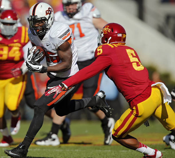 Oklahoma State 's Desmond Roland (26) runs past Iowa State's Jacques Washington (5) during the college football game between the Oklahoma State University Cowboys (OSU) and the Iowa State University Cyclones (ISU) at Jack Trice Stadium in Ames, Iowa, on Saturday, Oct. 26, 2013.  Photo by Chris Landsberger, The Oklahoman