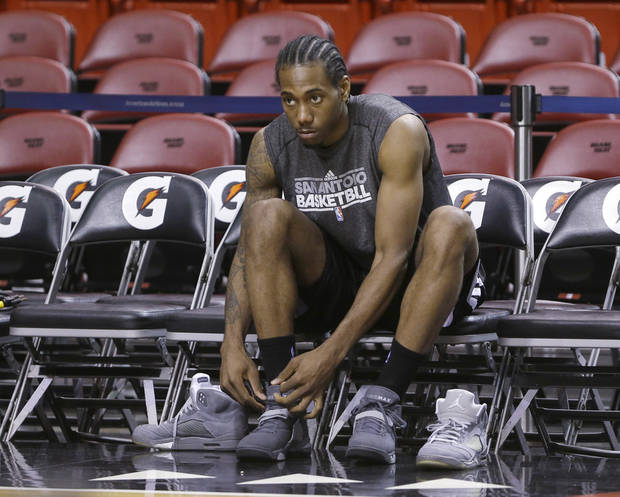 San Antonio Spurs small forward Kawhi Leonard changes shoes before basketball practice on Saturday, June 8, 2013, at the American Airlines Arena in Miami. The Miami Heat and the Spurs are to play Game 2 of the NBA Finals, Sunday. (AP Photo/Wilfredo Lee) ORG XMIT: AAA109
