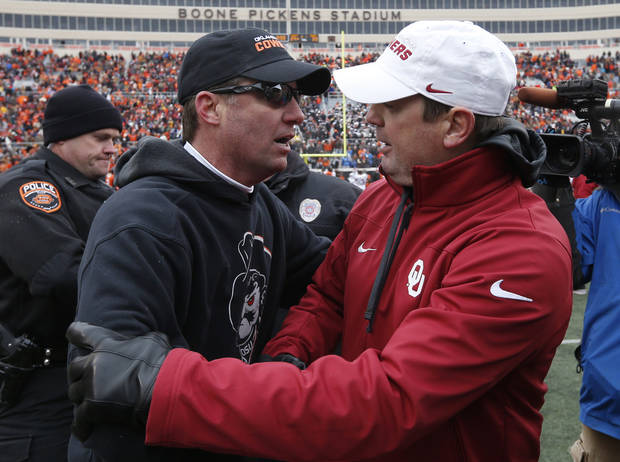 Oklahoma State head coach Mike Gundy, left, and Oklahoma head coach Bob Stoops, right, meet at midfield following their NCAA college football game in Stillwater, Okla., Saturday, Dec. 7, 2013. Oklahoma won 33-24. (AP Photo/Sue Ogrocki)