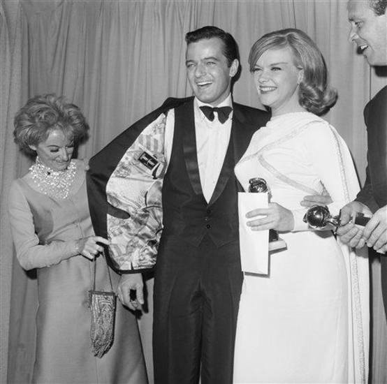 Phyllis Diller checks out  Robert Goulet's coat  as they pose for photographers at  the Hollywood Foreign Press Association and Golden Globe Awards  in Hollywood, Calif.,  January 31, 1966.     At right is Ann Francis. (AP Photo/ Harold Matosian)