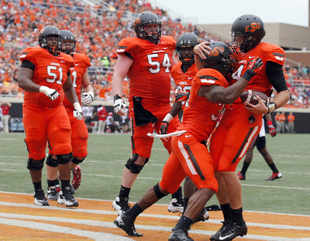 Oklahoma State's J.W. Walsh (4) celebrates a rushing touchdown with Jeremy Smith (31) during a college football game between Oklahoma State University (OSU) and the University of Louisiana-Lafayette (ULL) at Boone Pickens Stadium in Stillwater, Okla., Saturday, Sept. 15, 2012. Photo by Sarah Phipps, The Oklahoman
