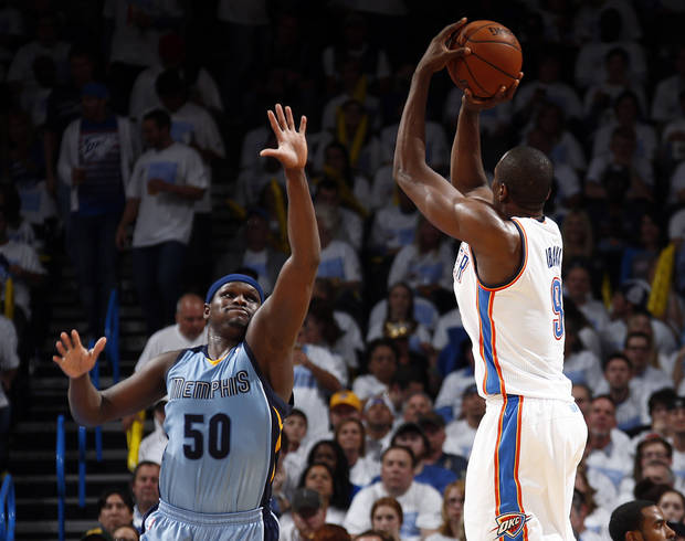 Oklahoma City's Serge Ibaka (9) shoots a 3-point shot over Memphis' Zach Randolph (50) during Game 5 in the first round of the NBA playoffs between the Oklahoma City Thunder and the Memphis Grizzlies at Chesapeake Energy Arena in Oklahoma City, Tuesday, April 29, 2014. Photo by Sarah Phipps, The Oklahoman