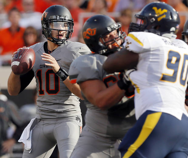 Oklahoma State's Clint Chelf (10) looks to pass in the first quarter during a college football game between Oklahoma State University (OSU) and West Virginia University (WVU) at Boone Pickens Stadium in Stillwater, Okla., Saturday, Nov. 10, 2012. Photo by Nate Billings, The Oklahoman