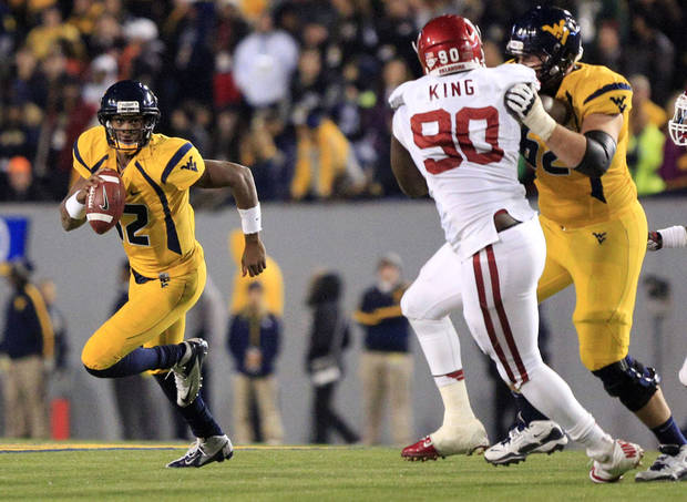 West Virginia quarterback Geno Smith (12) carries the ball as Curtis Feigt (62) blocks Oklahoma's David King (90) during the fourth quarter of their NCAA college football game against Oklahoma in Morgantown, W.Va., on Saturday, Nov. 17, 2012. Oklahoma won 50-49. (AP Photo/Christopher Jackson)