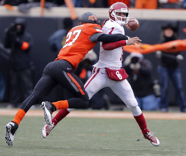 Oklahoma's Kendal Thompson (1) is hit by Oklahoma State's Lyndell Johnson (27) during the Bedlam college football game between the Oklahoma State University Cowboys (OSU) and the University of Oklahoma Sooners (OU) at Boone Pickens Stadium in Stillwater, Okla., Saturday, Dec. 7, 2013. Photo by Chris Landsberger, The Oklahoman