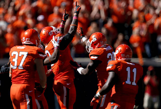Oklahoma State's Daytawion Lowe (8) ,middle, celebrates a interception during a college football game between Oklahoma State University (OSU) and Iowa State University (ISU) at Boone Pickens Stadium in Stillwater, Okla., Saturday, Oct. 20, 2012. Photo by Sarah Phipps, The Oklahoman