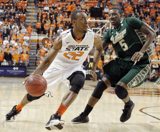Oklahoma State 's Markel Brown (22) drives past South Florida Bulls' Jawanza Poland (5) during the college basketball game between Oklahoma State University (OSU) and the University of South Florida (USF) on Wednesday , Dec. 5, 2012, in Stillwater, Okla.   Photo by Chris Landsberger, The Oklahoman
