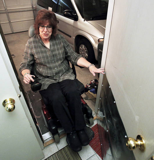 Debbie Perkins uses a ramp and wheelchair to enter her Norman home from her garage. She was diagnosed with multiple sclerosis in 1993 and has experienced some disability. PHOTOs BY STEVE SISNEY, THE OKLAHOMAN
