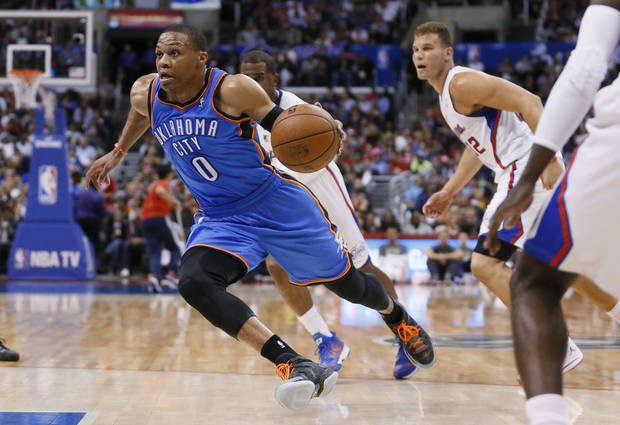 Oklahoma City Thunder guard Russell Westbrook drives past Los Angeles Clippers' Chris Paul, rear, and Blake Griffin, right, during the first half of an NBA basketball game in Los Angeles, Wednesday, April 9, 2014. (AP Photo/Danny Moloshok)