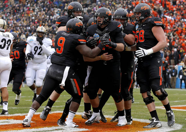 Oklahoma State&#039;s Jeremy Seaton (44) celebrates with Kye Staley (9), Daniel Koenig (58), and others after a touchdown during the Heart of Dallas Bowl football game between Oklahoma State University and Purdue University at the Cotton Bowl in Dallas, Tuesday, Jan. 1, 2013. Photo by Bryan Terry, The Oklahoman