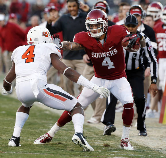 Oklahoma's Kenny Stills (4) stiff arms Oklahoma State's Justin Gilbert (4) forces him out of bounds during the second half of the Bedlam college football game in which  the University of Oklahoma Sooners (OU) defeated the Oklahoma State University Cowboys (OSU) 51-48 in overtime at Gaylord Family-Oklahoma Memorial Stadium in Norman, Okla., Saturday, Nov. 24, 2012. Photo by Steve Sisney, The Oklahoman