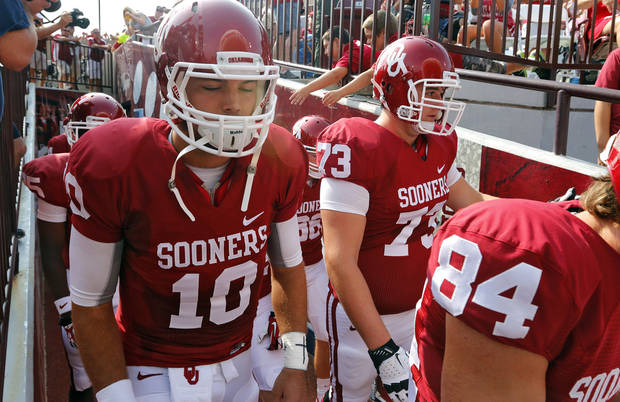 Oklahoma quarterback Blake Bell, left, takes the field before the Sooners' 51-20 win over Tulsa on Saturday. PHOTO BY CHRIS LANDSBERGER, THE OKLAHOMAN