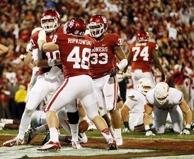 Oklahoma's Blake Bell (10) celebrates with Aaron Ripkowski (48) and Trey Millard (33) after rushing for a touchdown in the final minute of regulation during the Bedlam college football game between the University of Oklahoma Sooners (OU) and the Oklahoma State University Cowboys (OSU) at Gaylord Family-Oklahoma Memorial Stadium in Norman, Okla., Saturday, Nov. 24, 2012. The extra point on this touchdown tied the game. OU won, 51-48 in overtime. Photo by Nate Billings , The Oklahoman