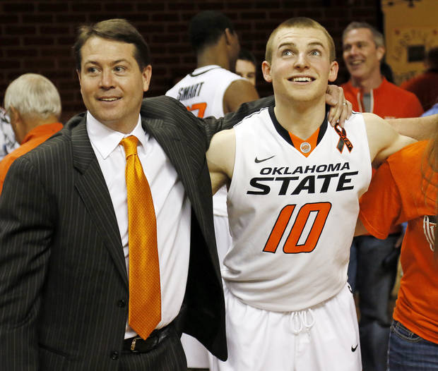OSU head coach Travis Ford stands with Phil Forte (10) for the singing of the alma mater after a men's college basketball game between Oklahoma State University and Texas Tech at Gallagher-Iba Arena in Stillwater, Okla., Saturday, Jan. 19, 2013. OSU won, 79-45. Photo by Nate Billings, The Oklahoman