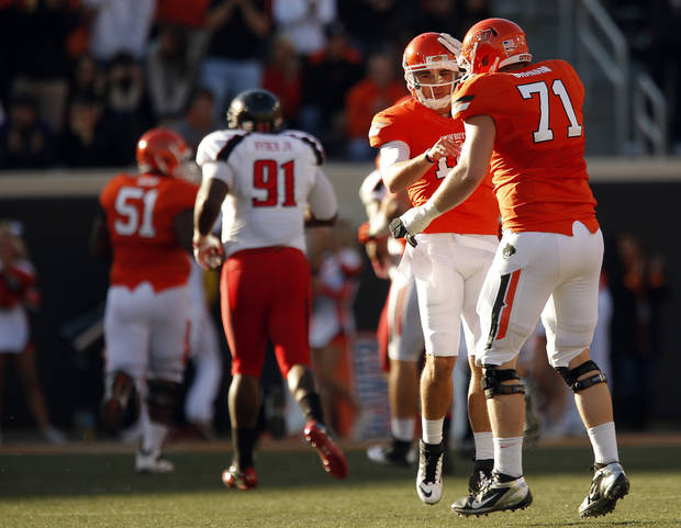 CELEBRATION: Oklahoma State's Clint Chelf (10) and Oklahoma State's Parker Graham (71) celebrate a Cowboy touchdown during a college football game between Oklahoma State University and the Texas Tech University (TTU) at Boone Pickens Stadium in Stillwater, Okla., Saturday, Nov. 17, 2012. Photo by Sarah Phipps, The Oklahoman