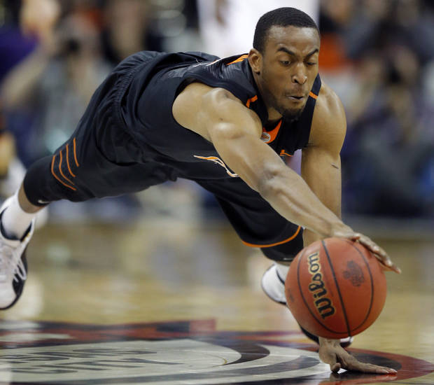 Oklahoma State guard Markel Brown dives for a loose ball during the first half of an NCAA college basketball game against Kansas in the quarterfinals of the Big 12 Conference men's tournament in Kansas City, Mo., Thursday, March 13, 2014. (AP Photo/Orlin Wagner)
