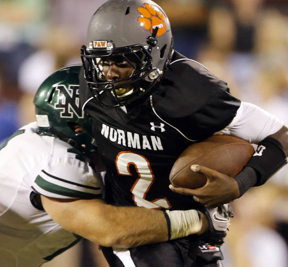 Norman High quarterback Jakcob Dean is brought down by Norman North's Mason Volk at Gaylord Family-Oklahoma Memorial Stadium in Norman, Okla., on Thursday, Sept. 5, 2013. Photo by Steve Sisney, The Oklahoman