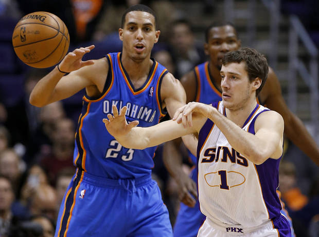 Phoenix Suns guard Goran Dragic, of Slovenia, passes as Oklahoma City Thunder guard Kevin Martin (23) defends during the first half of an NBA basketball game, Monday, Jan. 14, 2013, in Phoenix. (AP Photo/Matt York) ORG XMIT: PNU108
