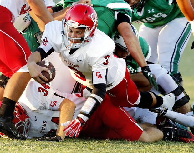 Titan quarterback Stevie Thompson stretches for a first down as the Carl Albert Titans play the Bishop McGuinness Irish on Friday, Oct. 4, 2013 in Oklahoma City, Okla.  Photo by Steve Sisney, The Oklahoman
