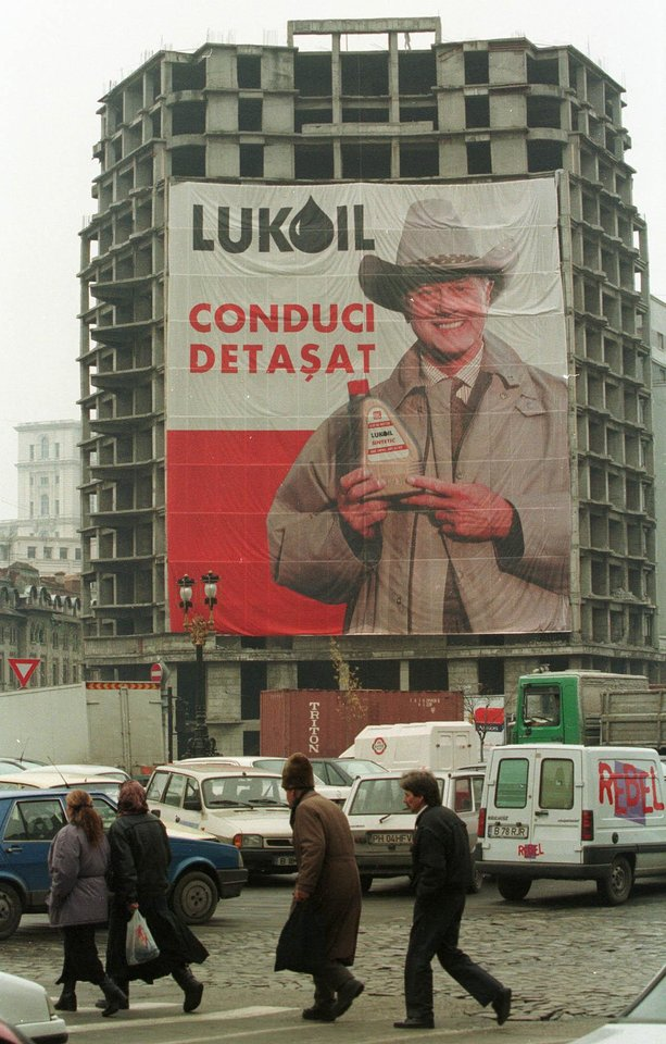 Photo -   FILE - In this Thursday Nov. 18, 1999 file photo, people cross the street in downtown Bucharest, Romania near an unfinished apartment building draped with a poster of U.S. actor Larry Hagman as J.R. Ewing from the television show