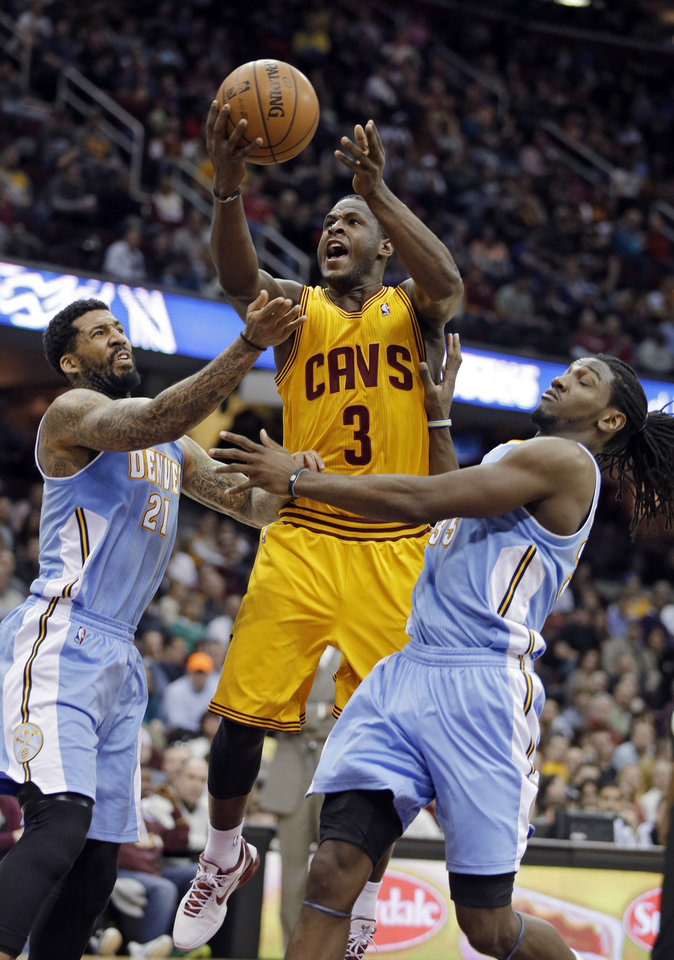 Photo - Cleveland Cavaliers' Dion Waiters (3) shoots between Denver Nuggets' Wilson Chandler, left, and Kenneth Faried in the second quarter of an NBA basketball game Saturday, Feb. 9, 2013, in Cleveland. (AP Photo/Mark Duncan)
