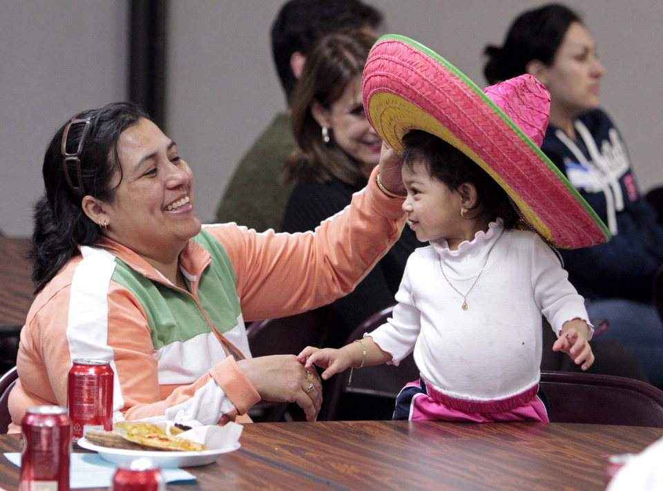 Ana Judith Ramirez tries a table decoration on her daughter Maggie at the Norman Public School District's Spanish Family Night on Thursday, March 8, 2012, in Norman, Okla.   Photo by Steve Sisney, The Oklahoman