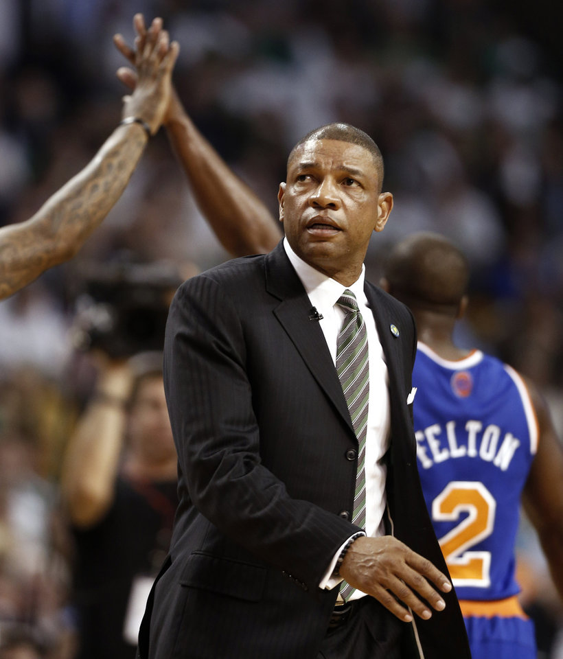 Photo - New York Knicks' Raymond Felton (2) gets a high-five from a teammate as Boston Celtics' Doc Rivers walks onto the court after calling a time out during the second quarter of Game 3 of a first-round NBA basketball playoff series in Boston, Friday, April 26, 2013. (AP Photo/Winslow Townson)