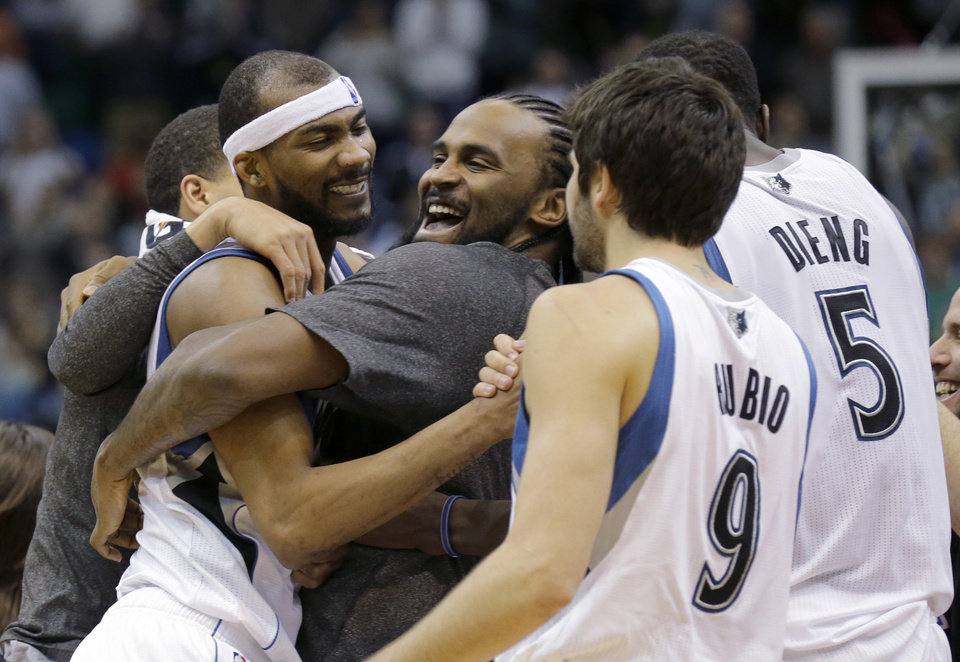 Photo - Minnesota Timberwolves forward Corey Brewer, left,  celebrates with teammates Ronny Turiaf, center, of France; Ricky Rubio (9), of Spain; and Gorgui Dieng (5) after the Timberwolves defeated the Houston Rockets 112-110 in an NBA basketball game in Minneapolis, Friday, April 11, 2014. (AP Photo/Ann Heisenfelt)