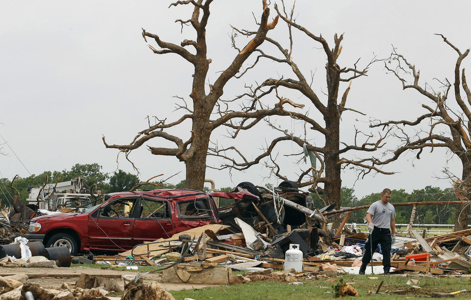 Photo - Crushed autos sit amid the rubble as emergency personnel continue search efforts to locate people in that are unaccounted for in the destroyed Rancho Brazos neighborhood of Granbury, Texas, Thursday, May 16, 2013. Ten tornadoes touched down in several small communities in North Texas overnight, leaving at least six people dead, dozens injured and hundreds homeless. Emergency responders were still searching for missing people Thursday afternoon. (AP Photo/The Fort Worth Star-Telegram, Paul Moseley)  MAGS OUT; (FORT WORTH WEEKLY, 360 WEST); INTERNET OUT