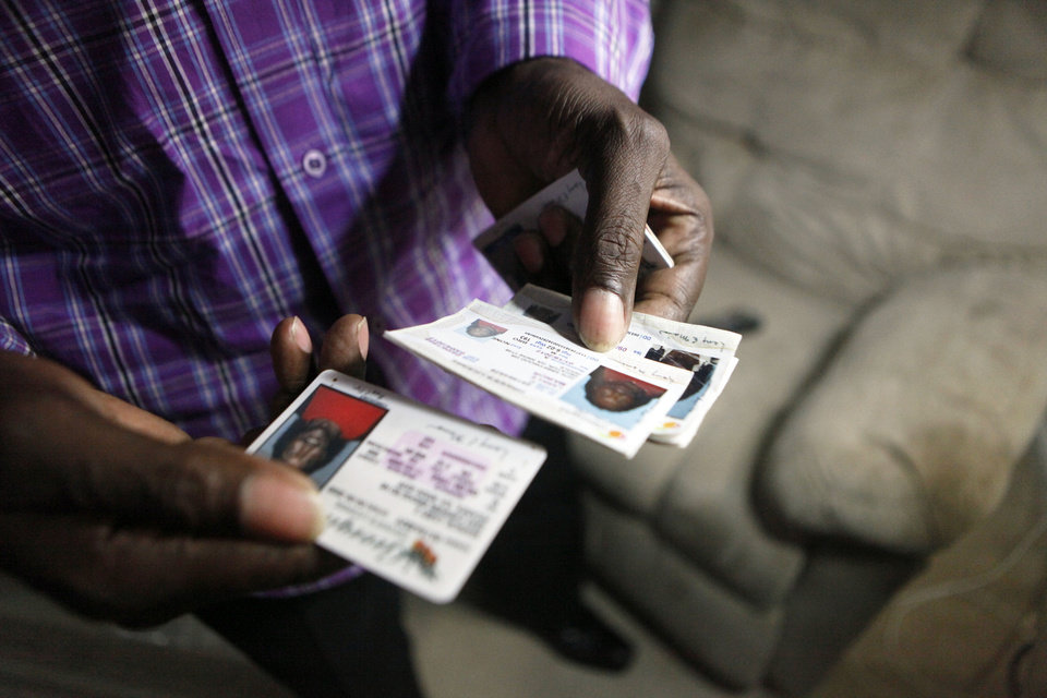 Photo - Veteran Larry Mainor, 48, looks at his photo ID's to see how his health has improved since ending his 30 years of homelessness while at his home, Saturday, Aug. 17, 2013, in Decatur, Ga. Atlanta's