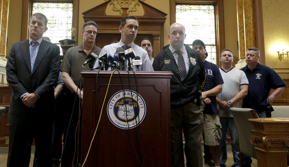 Photo - Jersey City Mayor Steven Fulop, center, addresses the media during a news conference talking about an early morning shooting which lead to a suspect and a Jersey City Police Department officer killed, Sunday, July 13, 2014, in Jersey City, N.J. Officer Melvin Santiago was shot in the head while still in his police vehicle as he and his partner responded to an armed robbery call at about 4.a.m., Fulop said. The Mayor said officers responding to the robbery call shot and killed the man who shot Santiago. (AP Photo/Julio Cortez)