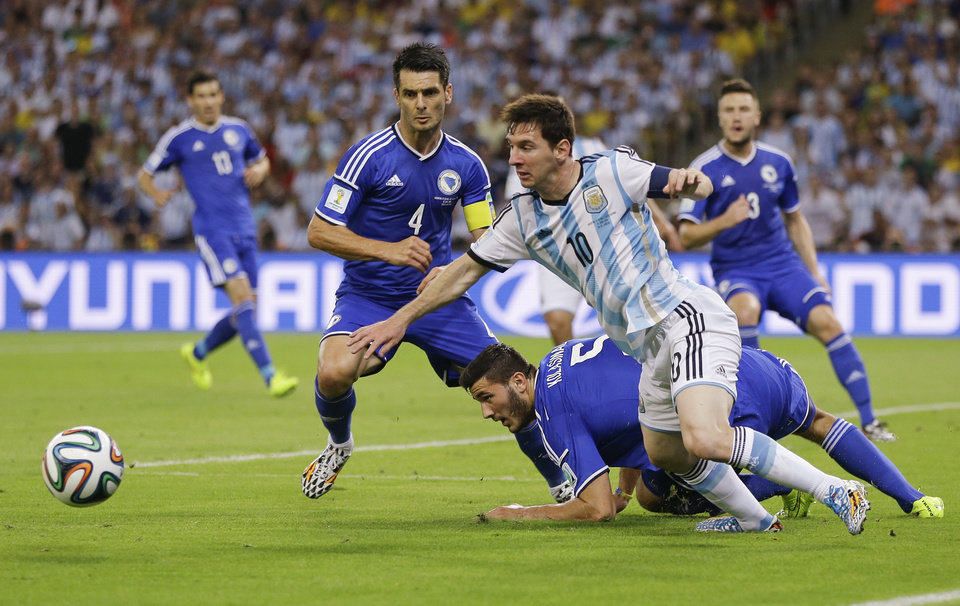 Photo - Argentina's Lionel Messi (10) scrambles to get back to the ball against Bosnia defenders Emir Spahic (4) and Sead Kolasinac (5) during their group F World Cup soccer match at the Maracana Stadium in Rio de Janeiro, Brazil, Sunday, June 15, 2014.  (AP Photo/Kirsty Wigglesworth)