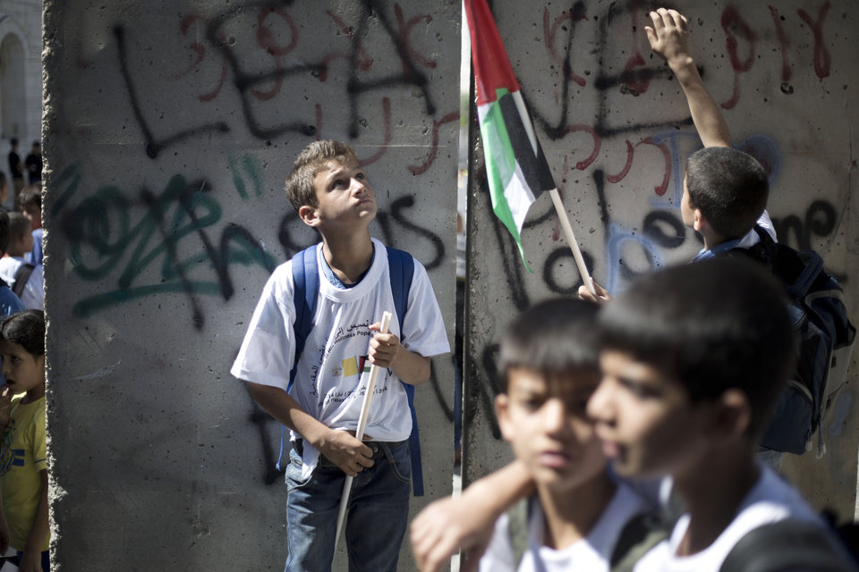 Photo - Palestinian children wait for Pope Francis at Israel's separation barrier near the Church of the Nativity, traditionally believed to be the birthplace of Jesus Christ in the Palestinian West Bank city of Bethlehem on Sunday, May 25, 2014. Francis called the Israeli-Palestinian stalemate