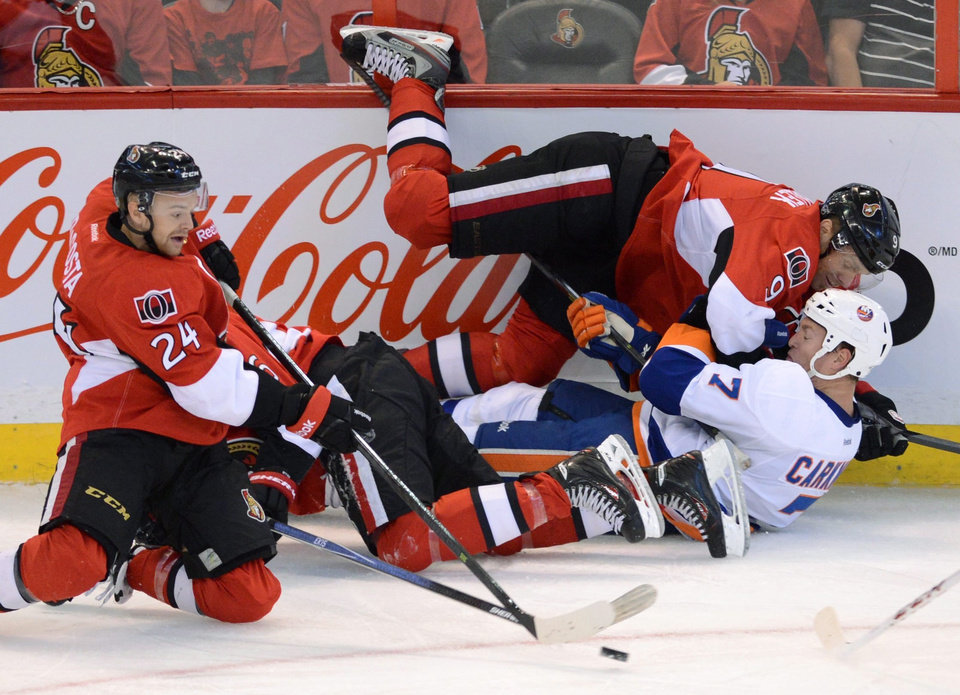 Photo - Ottawa Senators' Stephane De Costa moves the puck as teammate Milan Michalek takes New York Islanders' Matt Carkner to the ice during the first period of a preseason NHL hockey game in Ottawa, Ontario, on Sunday, Sept. 29, 2013. (AP Photo/The Canadian Press, Sean Kilpatrick)
