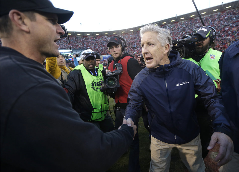 Photo - FILE - In this Dec. 8, 2013, file photo, San Francisco 49ers head coach Jim Harbaugh, left, shakes hands with Seattle Seahawks head coach Pete Carroll, right, after an NFL football game in San Francisco. The 49ers defeated the Seahawks 19-17. The Seahawks host the 49ers in the NFC championship on Sunday. (AP Photo/Marcio Jose Sanchez)