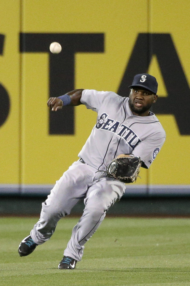 Photo - Seattle Mariners center fielder Abraham Almonte looks to catch a fly ball hit by Los Angeles Angels' David Freese during the first inning of a baseball game on Wednesday, April 2, 2014, in Anaheim, Calif. Almonte made the catch for the out. (AP Photo/Jae C. Hong)
