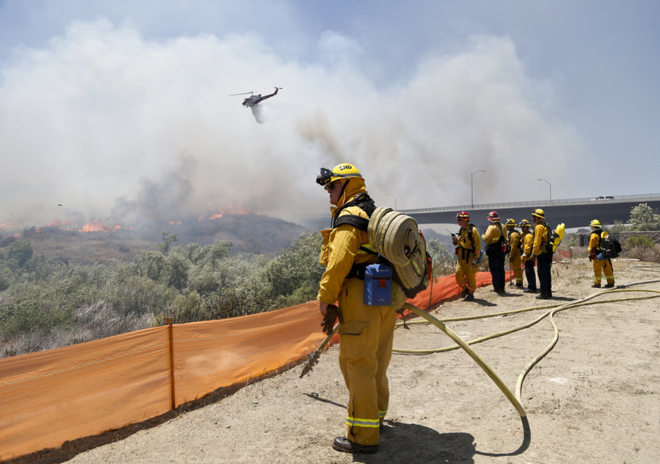 Photo - Firefighters watch from a ridge as a helicopter drops retardant on a out-of- control wild fire Tuesday, May 13, 2014, in San Diego.  (AP Photo)