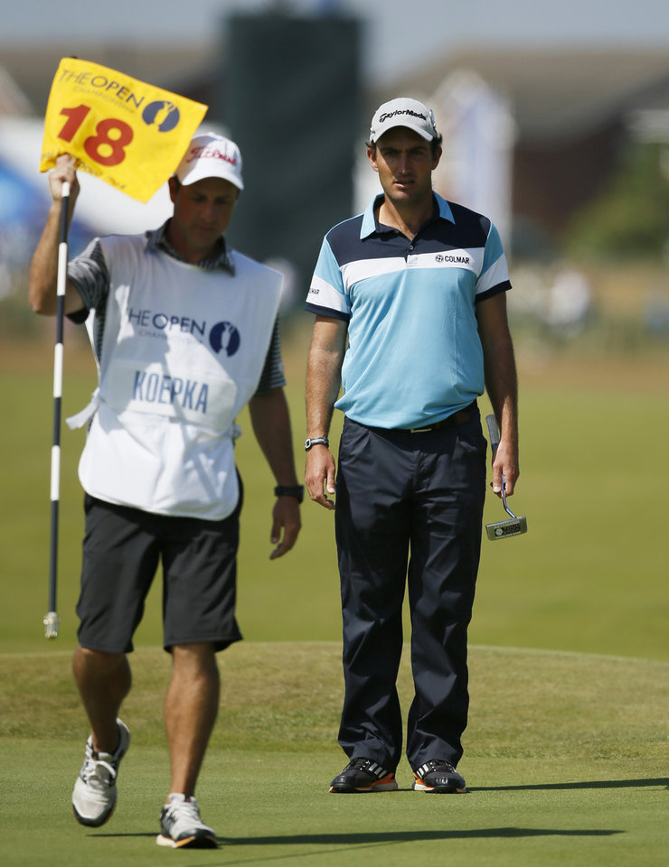 Photo - Edoardo Molinari of Italy waits to putt on the 18th green as Richard Elliot, the caddie of Brooks Koepka of the US, holds the flag during the first day of the British Open Golf championship at the Royal Liverpool golf club, Hoylake, England, Thursday July 17, 2014. (AP Photo/Alastair Grant)