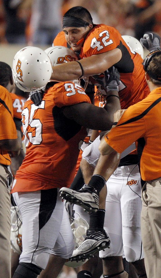 Photo - OSU's Justin Gent (42) celebrates his forced fumble with Chris Donaldson (95)during the college football game between the Oklahoma State University Cowboys (OSU) and the Troy University Trojans at Boone Pickens Stadium in Stillwater, Okla., Saturday, Sept. 11, 2010. Photo by Sarah Phipps, The Oklahoman