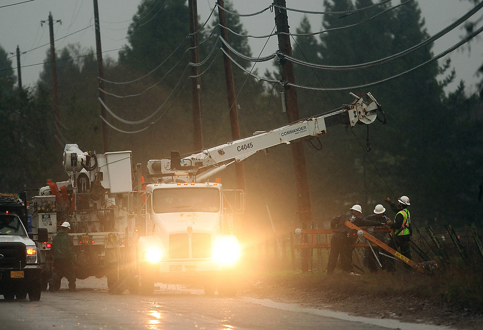 Utility crews work in the wind and rain to repair a power pole that was damaged by the overnight storm along Hall Road in Santa Rosa, Calif., on Sunday, Dec. 2, 2012. The National Weather Service issued flood warnings yesterday for both the Napa and Russian rivers. (AP Photo/The Press Democrat, Kent Porter)
