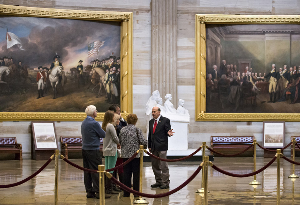 Photo - Rep. Louie Gohmert, R-Texas, escorts a group of constituents through the Capitol Rotunda during a lull in activity in the House of Representatives, Monday, Oct. 7, 2013, in Washington. The government partially shut down last week amid Washington gridlock and faces a make-or-break deadline later this month about the nation's borrowing power.  (AP Photo/J. Scott Applewhite)