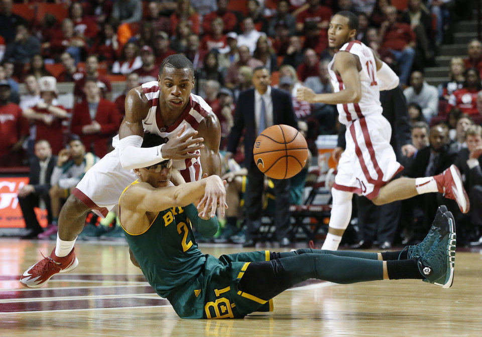 Photo - Baylor center Isaiah Austin, bottom, passes the ball in front of Oklahoma guard Buddy Hield in the second half of an NCAA college basketball game in Norman, Okla., Saturday, Feb. 8, 2014. Oklahoma won 88-72. Oklahoma guard Jordan Woodard(10) looks on. (AP Photo/Sue Ogrocki)