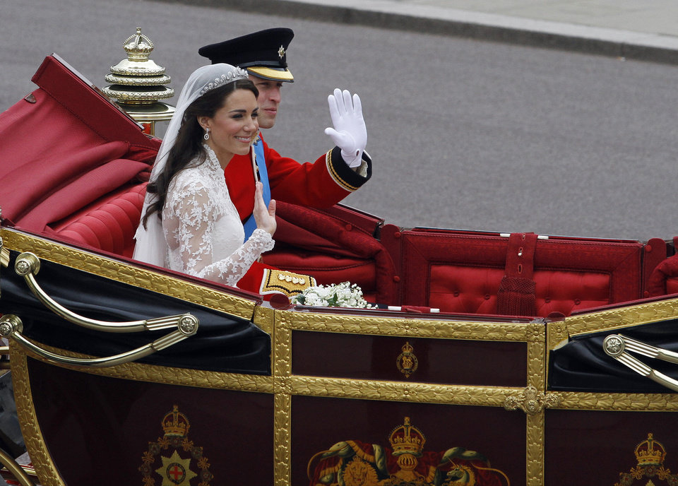 Photo - Britain's Prince William and his wife Kate, Duchess of Cambridge ride in a landau to Buckingham Palace after the Royal Wedding in London Friday, April, 29, 2011. (AP Photo/Matt Dunham)