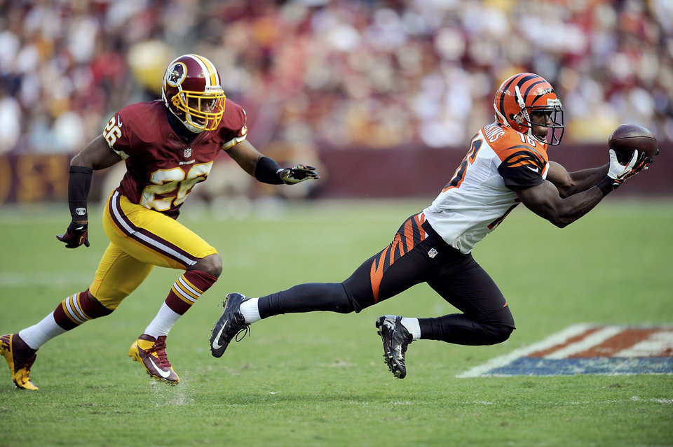Photo -   Cincinnati Bengals wide receiver Andrew Hawkins catches a pass while being defended by Josh Wilson of the Washington Redskins during the second half of an NFL football game in Landover, Md., Sunday, Sept. 23, 2012. (AP Photo/Nick Wass)